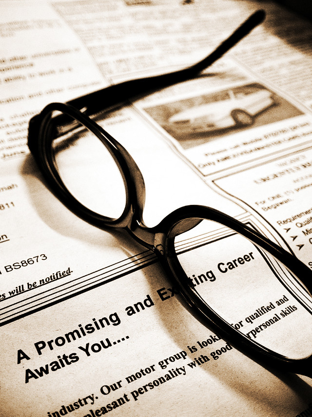A newspaper page with a pair of reading glasses