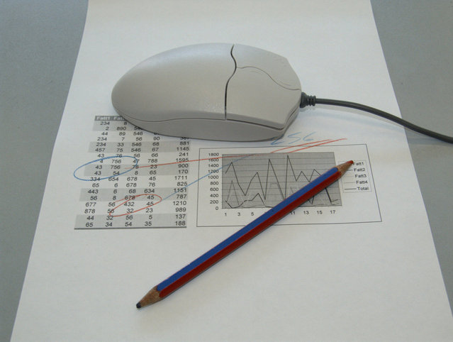 A Mouse sitting on top of a printed spreadsheet